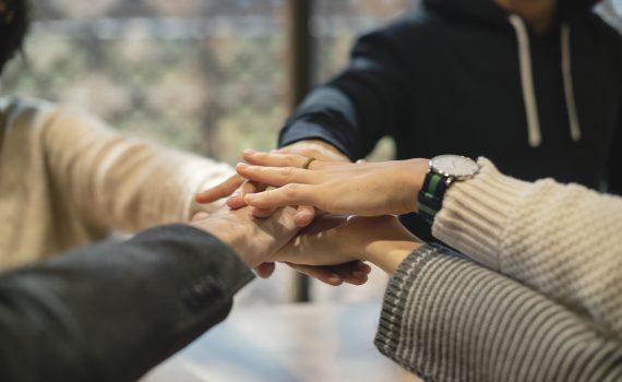 Groep deelnemers legt de handen op elkaar